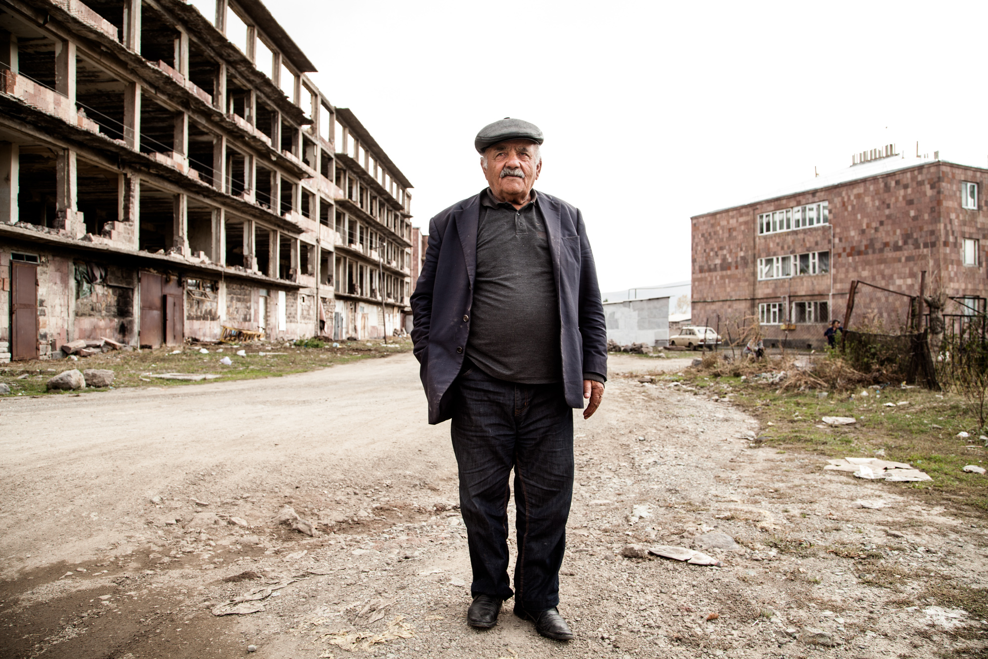 6 Décembre 1988. La terre tremble à 50 km d'Ashotsk, au nord-ouest de l'Arménie. Il est 11H40. Monsieur Stéfésov était chauffeur. Derrière lui, les ruines toujours debouts d'un des nombreux immeubles évacués.  Extraits du webdocumentaire   Ashotsk, aux confins de l'Arménie  .