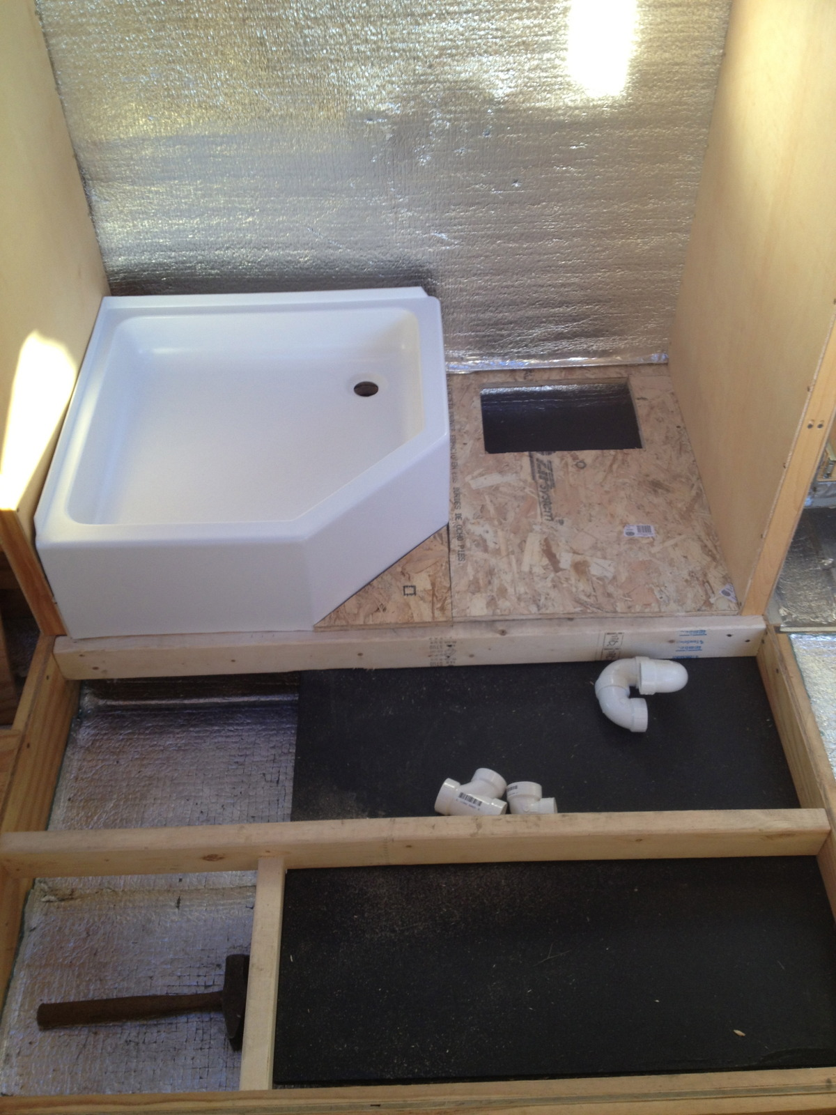 Shower pan in place with a hole cut in the floor for access to the gray water tank drain under the bathroom sink.
