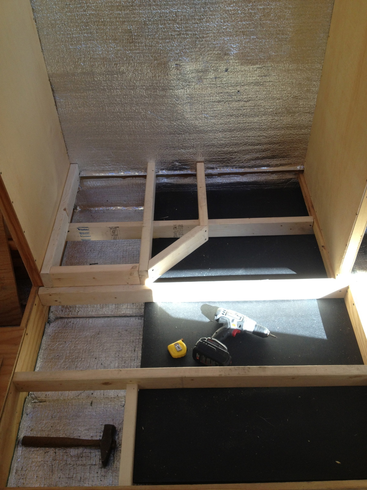 Continued framing of the gray water tank installation with the supports for the shower floor pan in place.