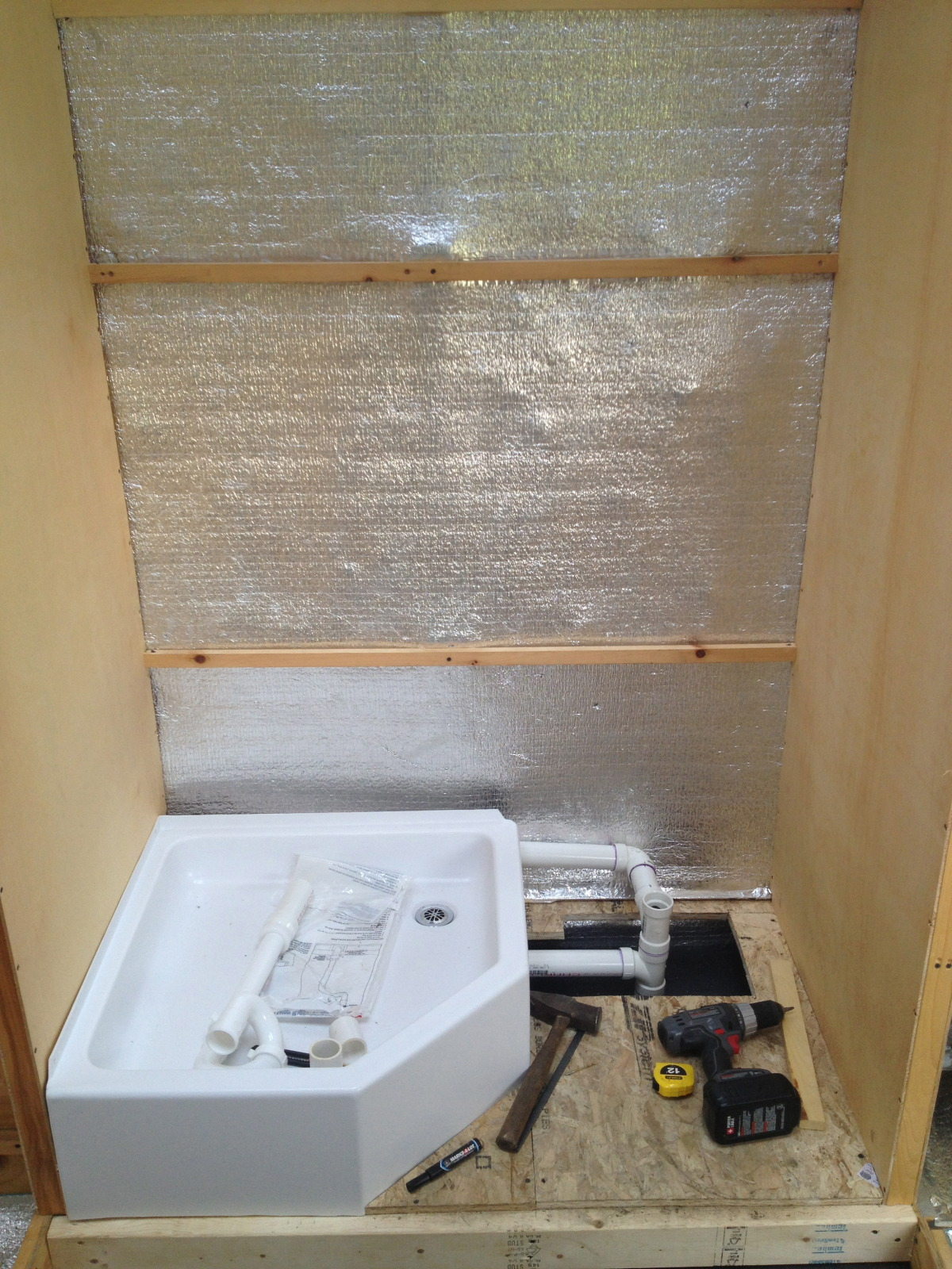 The kitchen sink, shower and bathroom sink all flow together into one pipe so there is only one hole draining into the top of gray water tank.  This shows the addition of another drain pipe running against the wall toward the front of the bus for the kitchen sink.