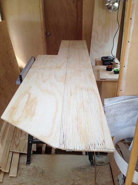 One of the plywood templates for a closet with numerous saw cuts scored into the surface.