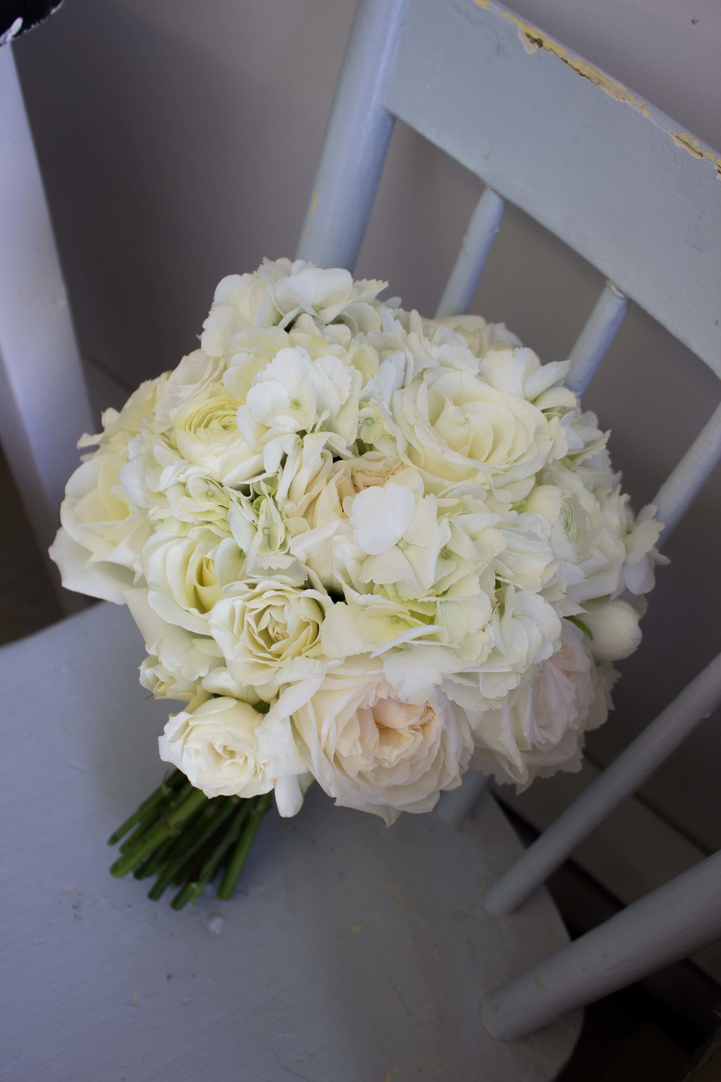Classic white bouquet with hydrangea, roses, ranunculus, and lisianthus.