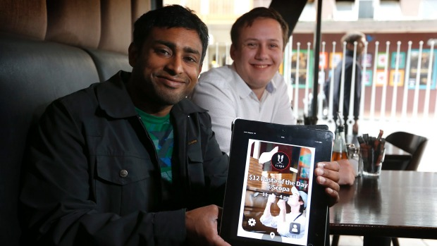 Danesh Abeyratne, left, and Connor Finlayson scroll through the current deals on their recently launched Hatcher