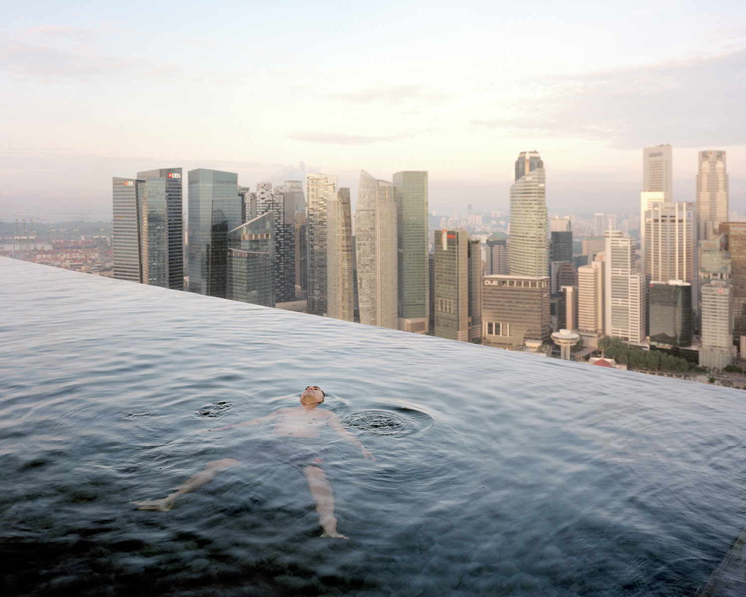 A man floats in the 57th-floor swimming pool of the Marina Bay Sands Hotel, with the skyline of the Singapore financial district behind him, 2013 © Paolo Woods & Gabriele Galimberti—INSTITUTE