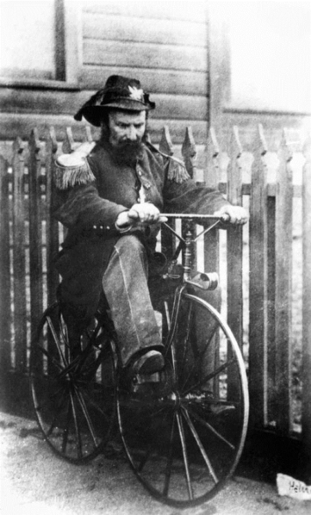 Detail from photograph of Emperor Norton taken in 1869 by Eadweard Muybridge (1830-1904). The scrap propped against the fence, in front of the bicycle, is inscribed with Muybridge's pseudonym: Helios.
