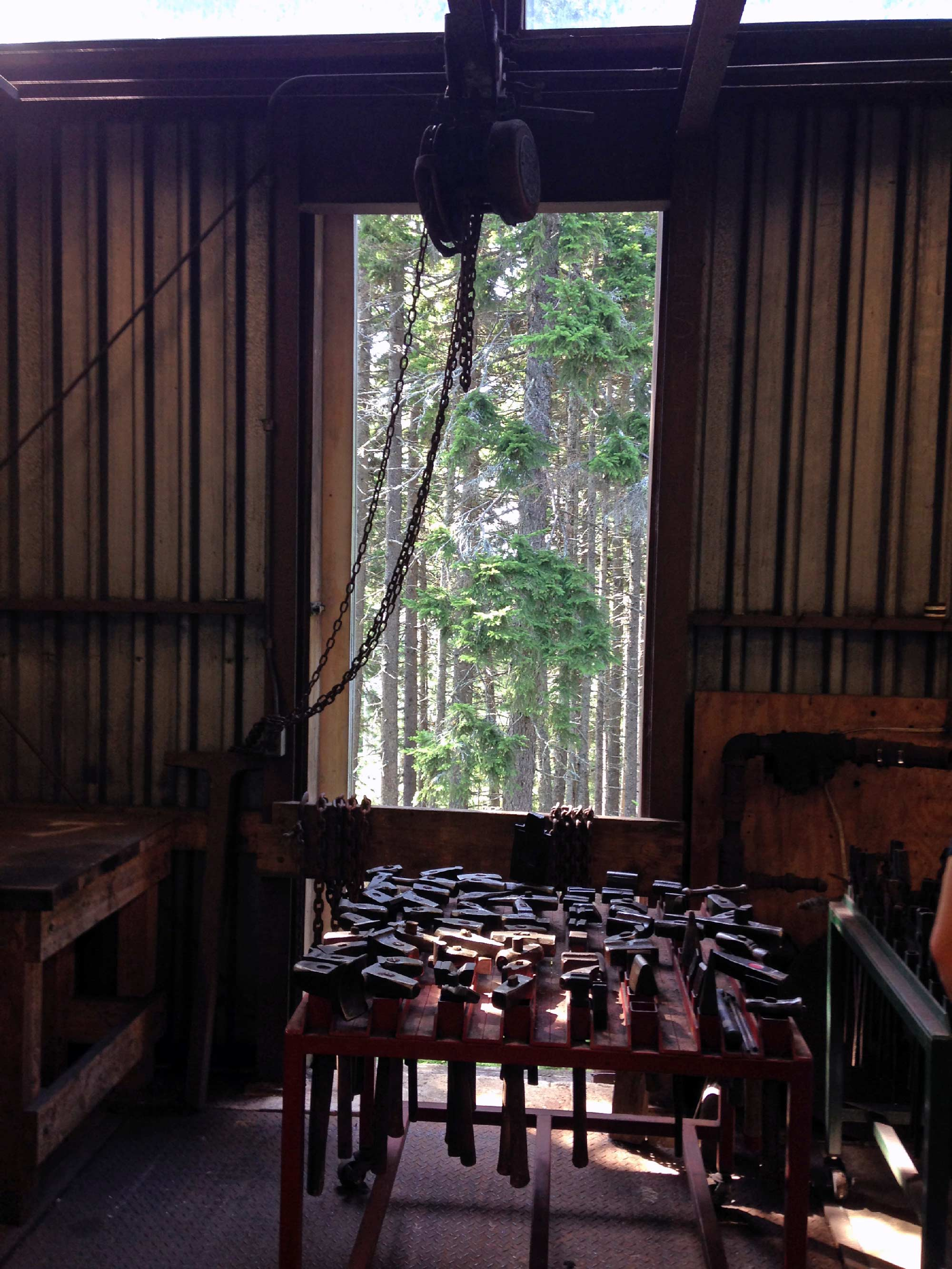 The view from Kaki's forge: across the hammers through the foundry window to the Spruces.