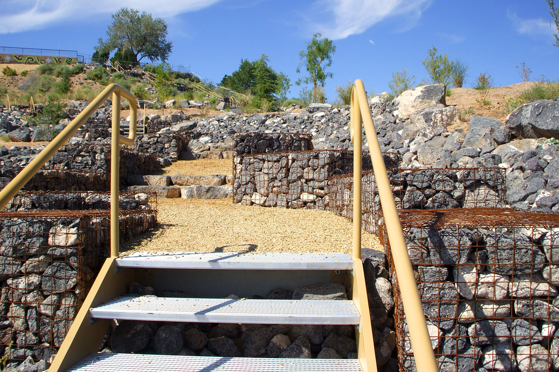 Use of industrial metal staircases fits right in to stone gabion landscape
