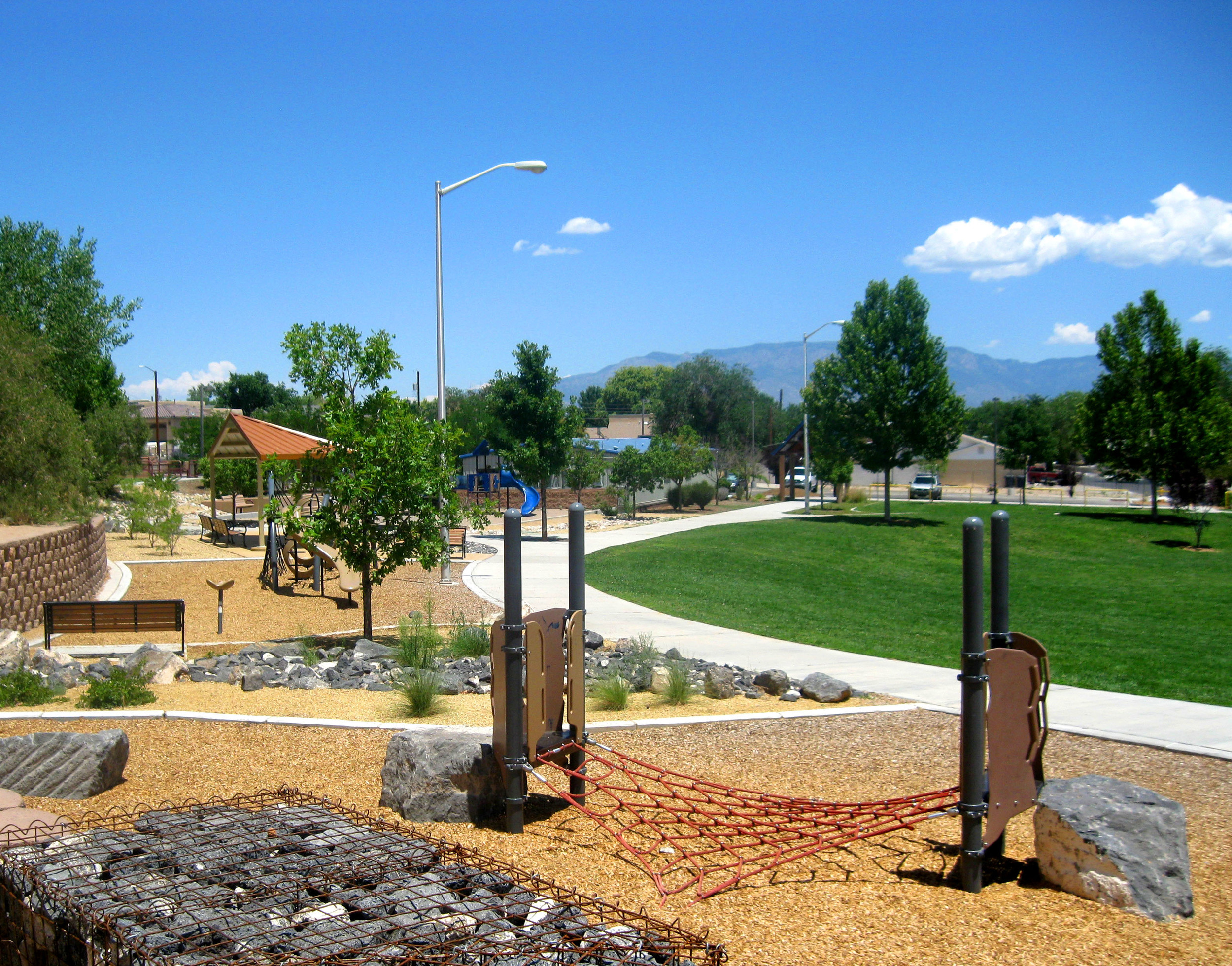 Play areas use locally available stone integrated with off-the-shelf play equipment