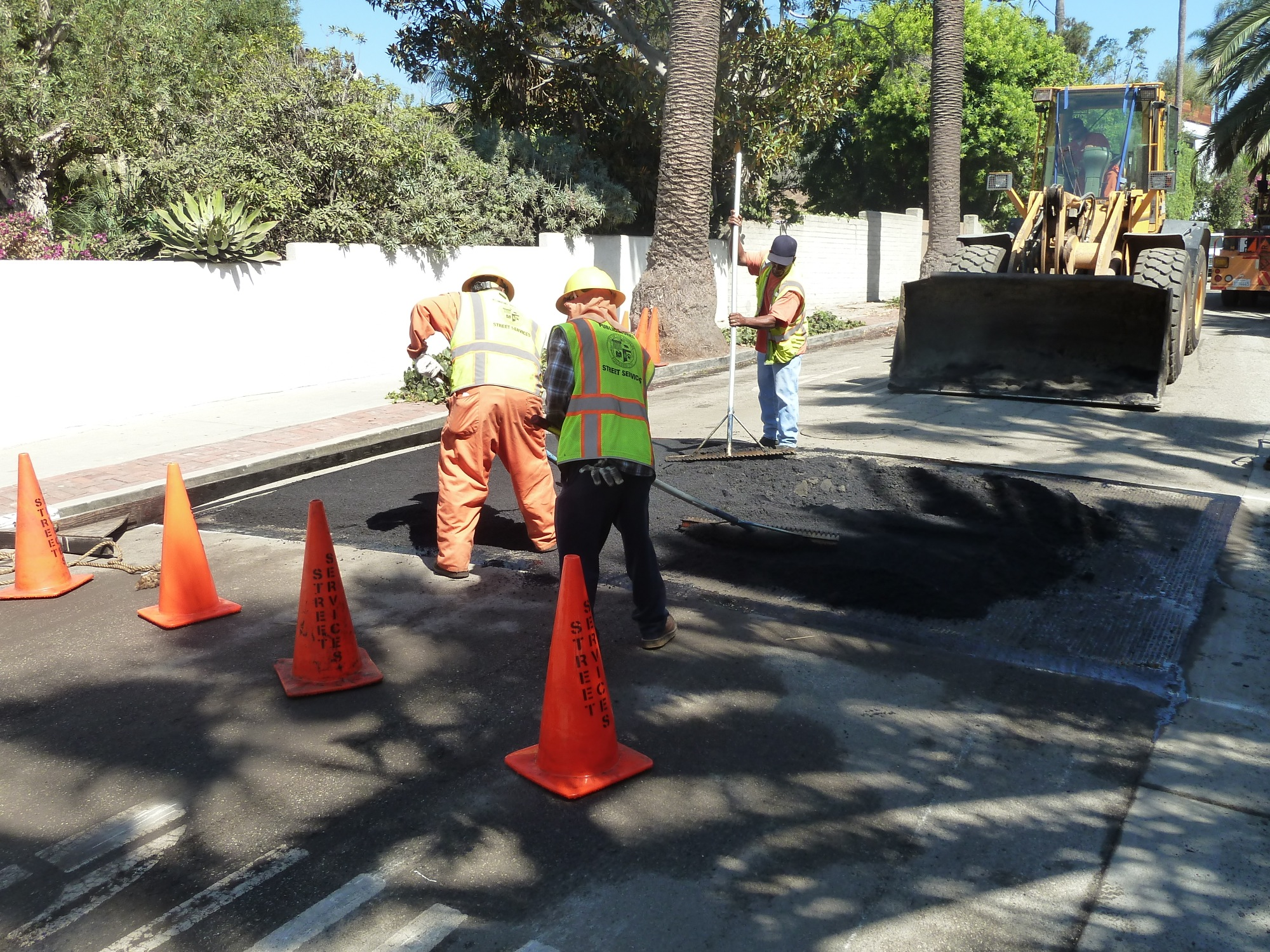 Spreading the asphalt with rakes