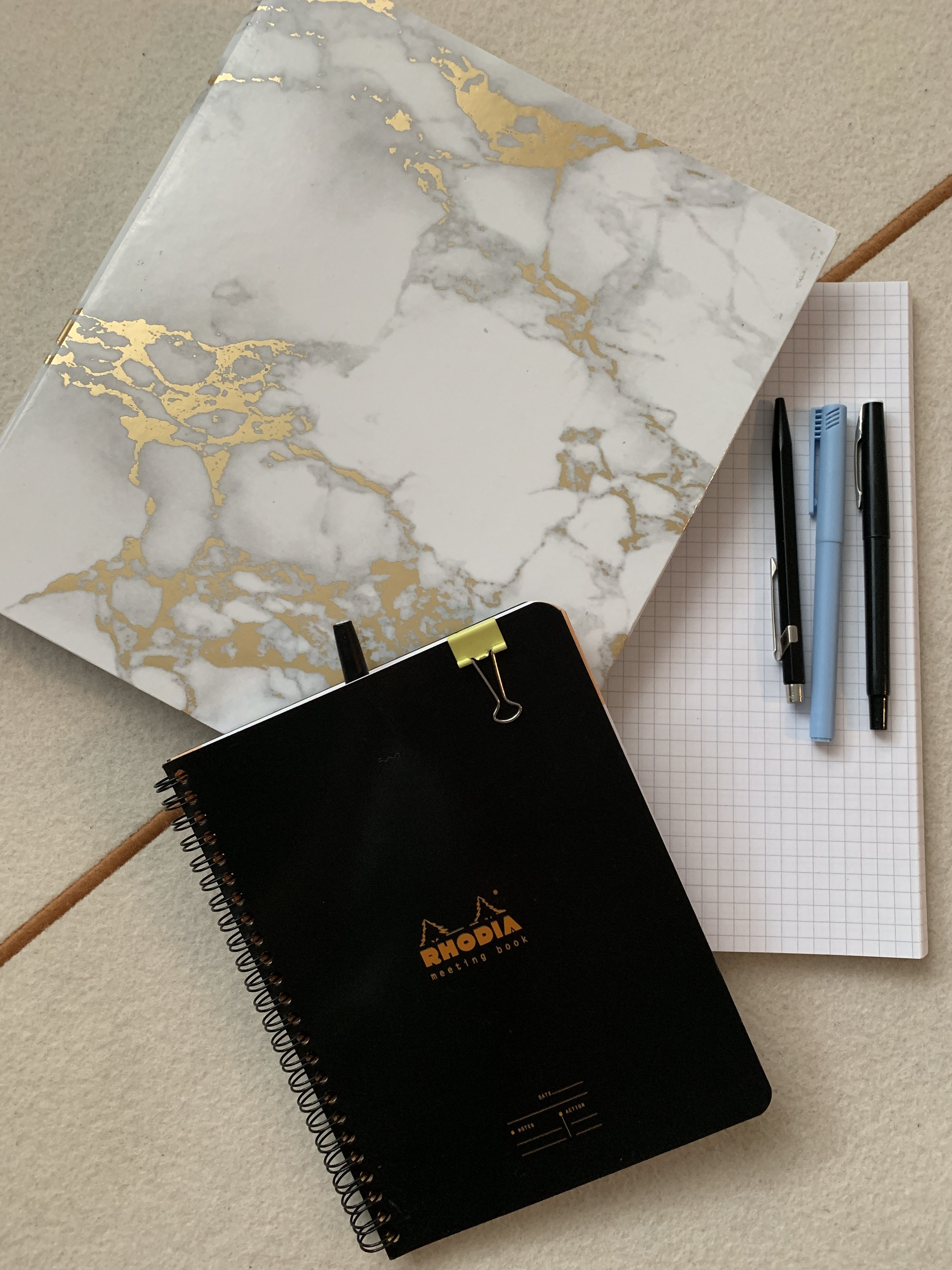 """Surprisingly loving this  cheap binder  from Amazon. And the  """"Meeting Book""""  from Rhodia has always been a favorite. Pens are  PaperMate Flair,   Normann Copenhagen felt pen,  and  Caran D'ache  metal ballpoint."""