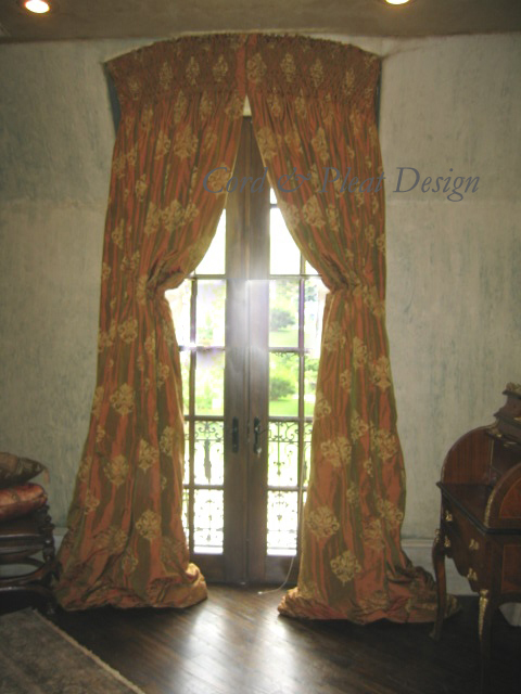 """These panels cover an eyebrow arched alcove and go back about 18"""" to the door creating almost a tent like effect. There is 12"""" of smocking at the top and are held back by faux Italian stringing. Designer: Jeannie Carpenter; Workroom: Cord & Pleat Design."""