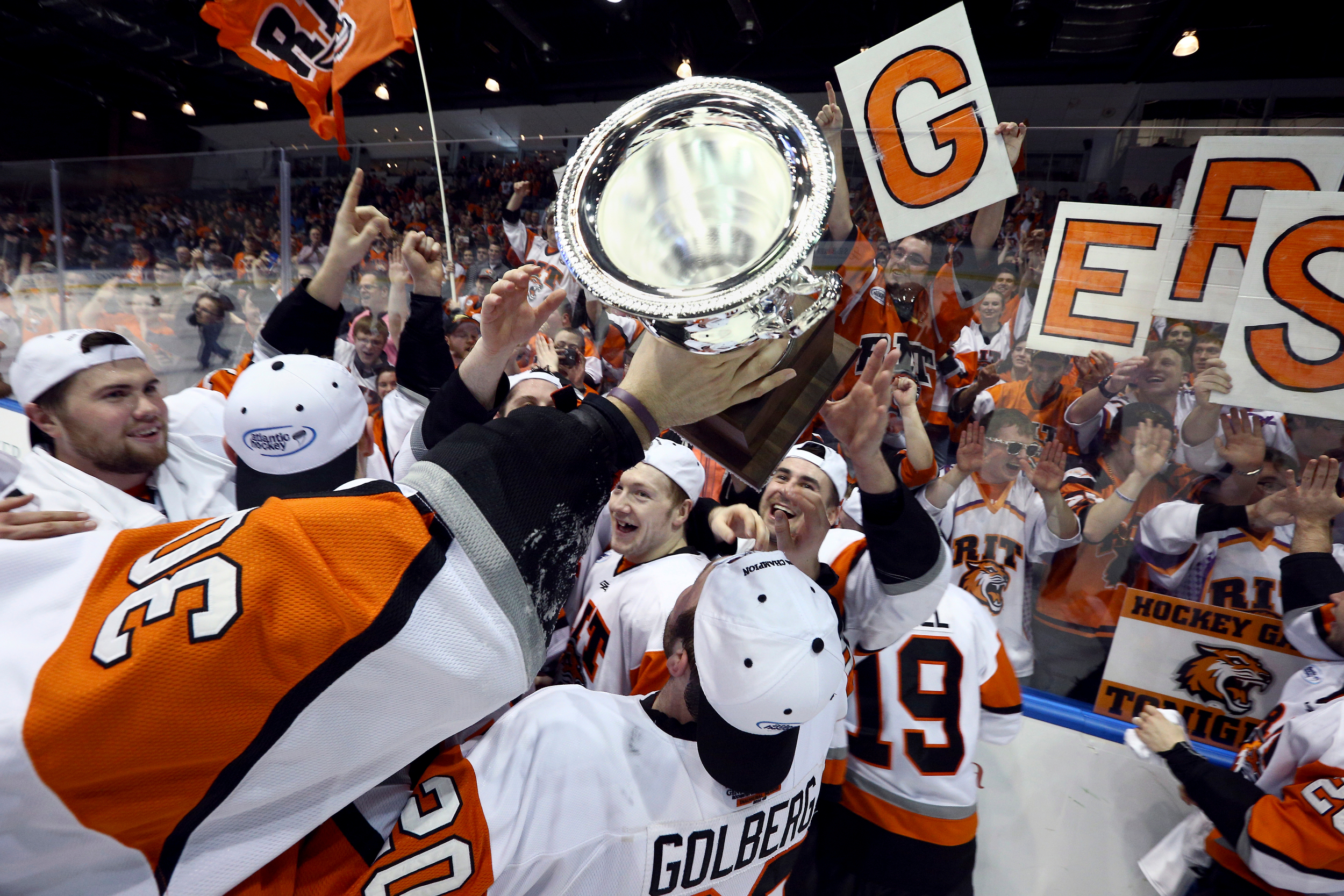 Rochester Institute of Technology men's hockey team celebrate while holding the Atlantic Hockey Conference championship trophy after defeating Mercyhurst University 5-1 at Blue Cross Arena on March 21, 2015 in Rochester, N.Y.
