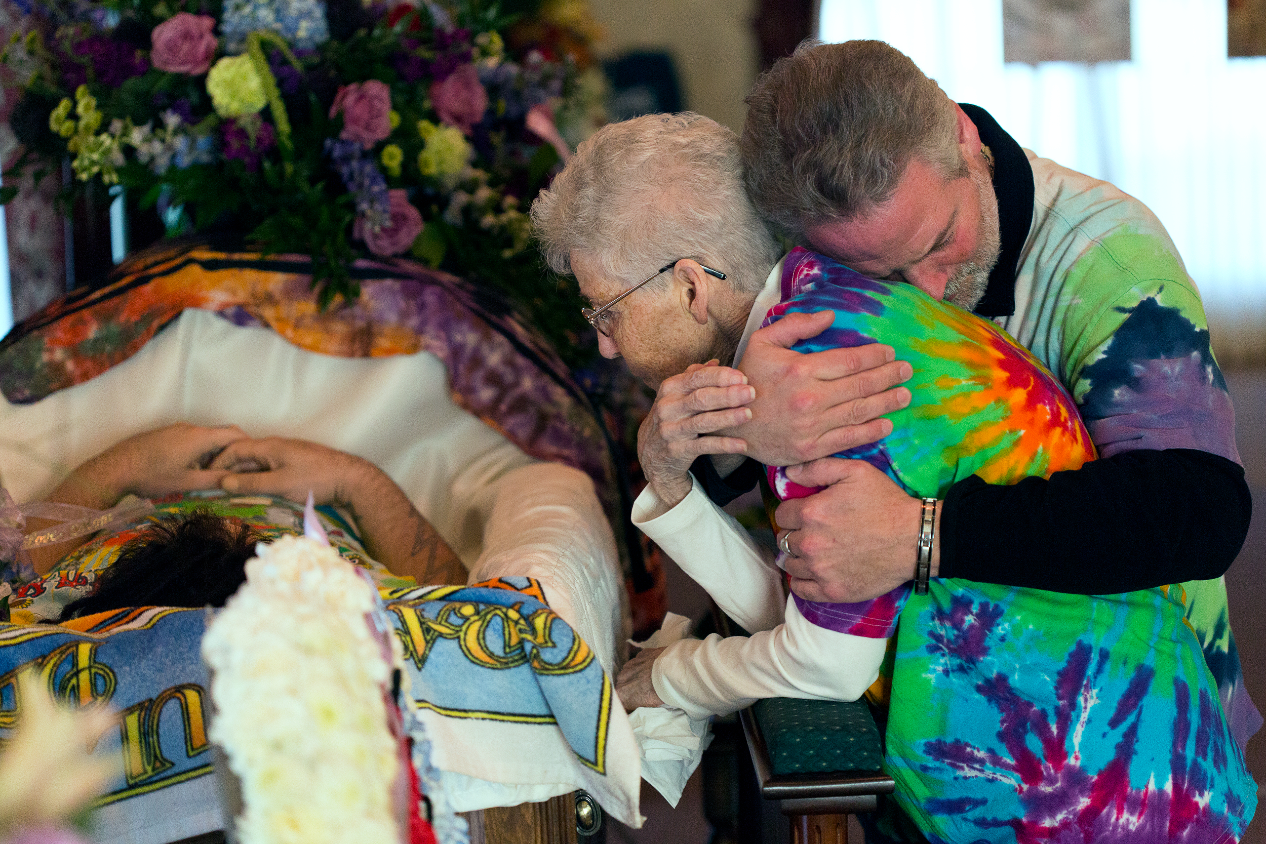 """Dee Doughty kneels next to her grandson Paul Doughty as her son Ron Doughty comforts her at Schepp & Son Family Funeral Home in Minoa, N.Y. on Nov. 17. 2015. """"I always wondered how Paul would take losing his grandparents, but I never thought they would be saying bye to him,"""" said Ron."""