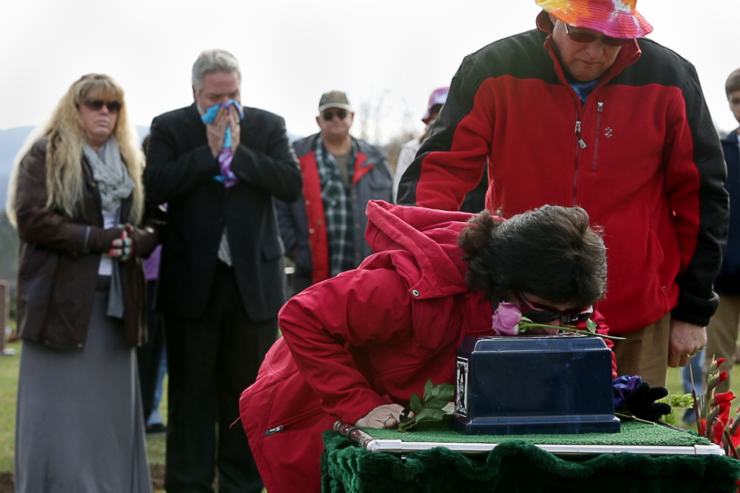 Mary Duck, Paul's mom, kisses her sons ashes as her husband Jeffrey Duck comforts her at Paul's burial on Nov. 21, 2015.