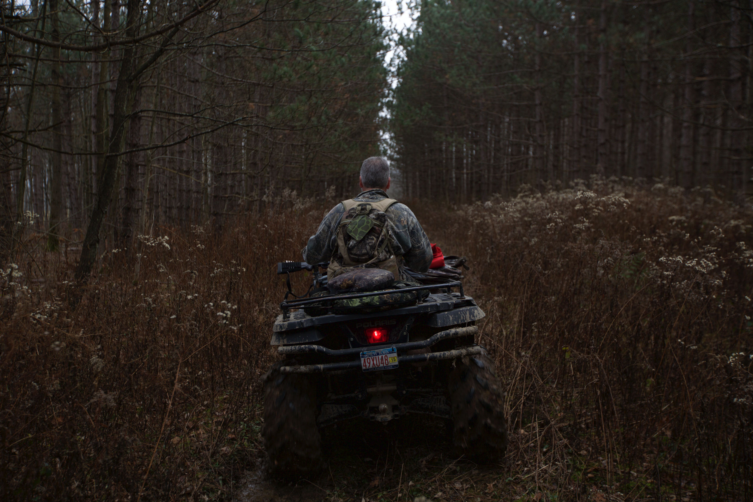 Ron rides his four-wheeler through the woods while hunting in Virgil, N.Y. Being in the woods relieves some of Ron's anxiety. Hunting is a big part of Ron's life but he has only been hunting once this season. Ron and Paul occasionally went hunting together.