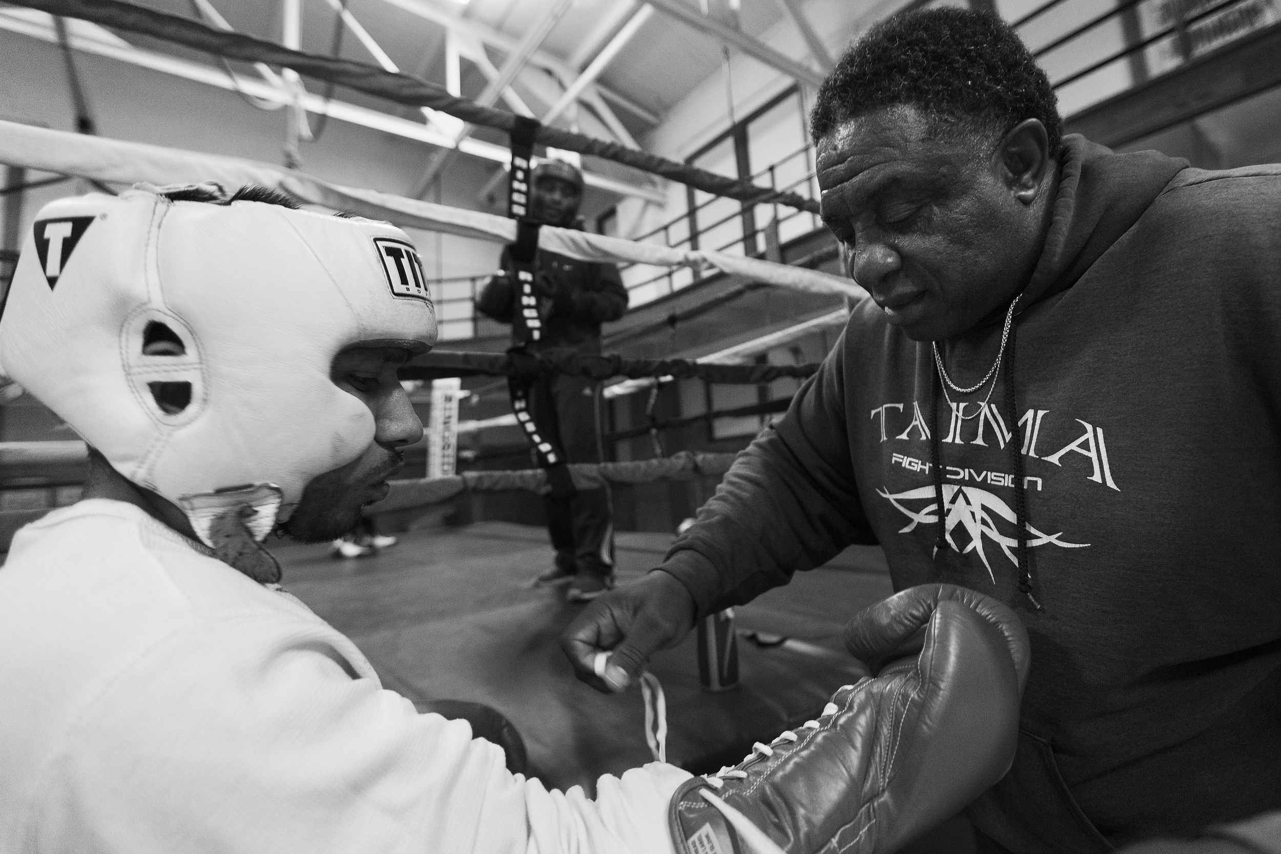 """Curtis Isaac, right, ties Santiago """"Santos"""" Garcia's gloved during boxing practice at Eastside Boxing Club in Kalamazoo, Mich. on May 17, 2016. Garcia won the Michigan Golden Glove novice class state championship at the 108 pound weight class in 2015 and 2016. (Bryan Bennett 