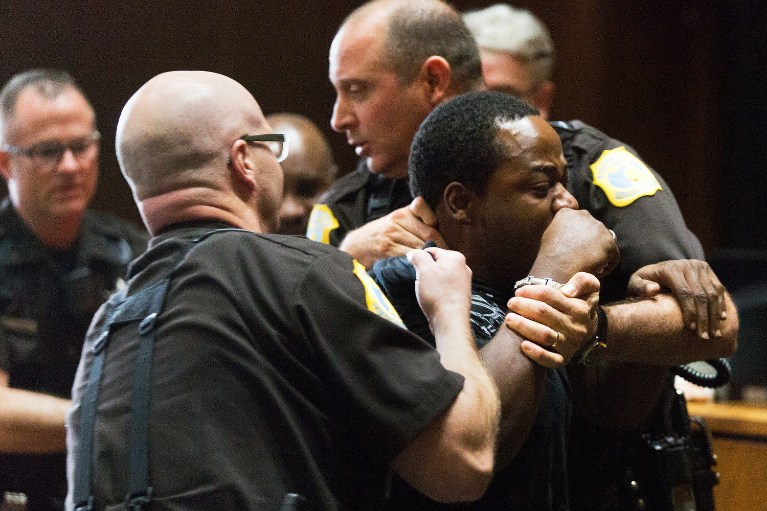Willie Warren, uncle to 17-year-old Temetrion Hegler, is restrained by officers after attempting to attack Bruce Embry, who murdered Hegler, during Embry's first degree murder sentencing at Kalamazoo County Courthouse in Kalamazoo, Mich. on Monday, Aug. 15, 2016. Embry was sentenced to life in prison without the possibility of parole.