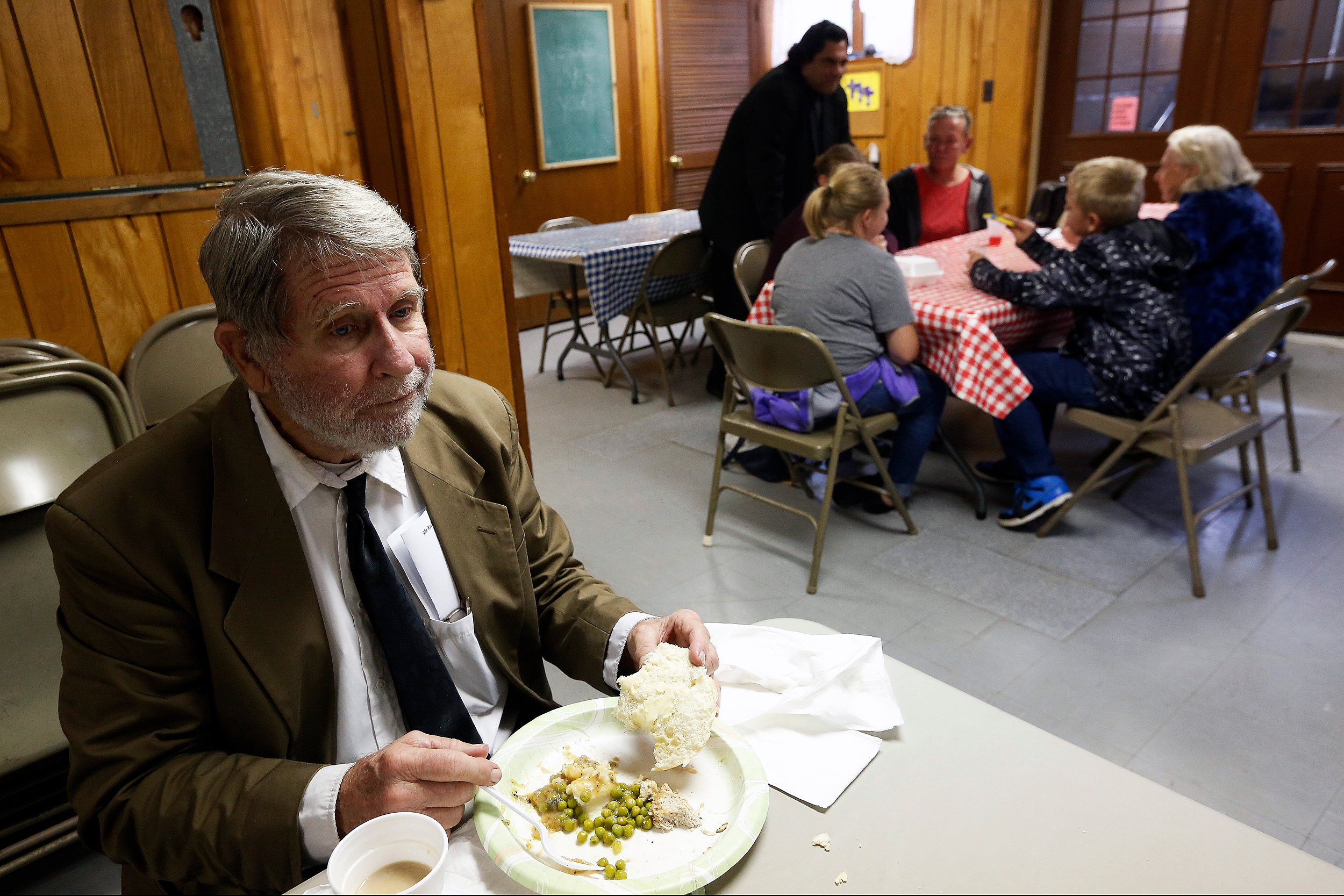 Ron eats lunch alone after church. Free meals are provided to people that attend church.