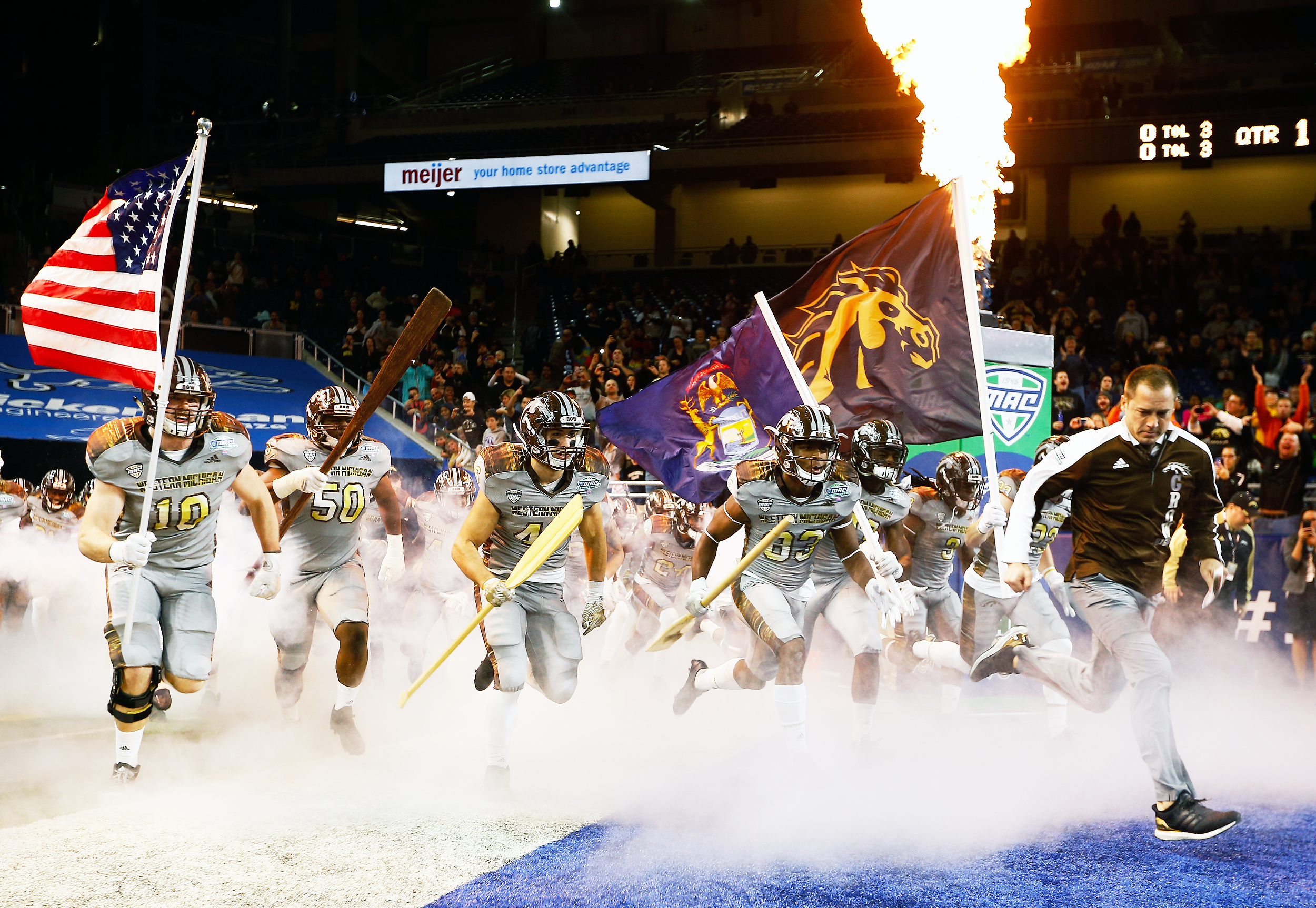 """The Broncos prepare to take on the Ohio Bobcats for the Mid-American Conference championship game at Ford Field in Detroit on Dec. 2, 2016. Bronco players rush the field carrying oars, a gesture symbolizing their mantra, """"Row the Boat."""" Broncos' coach P.J. Fleck began the tradition following his son's death in 2011. He uses the saying to encourage his players to never give up."""