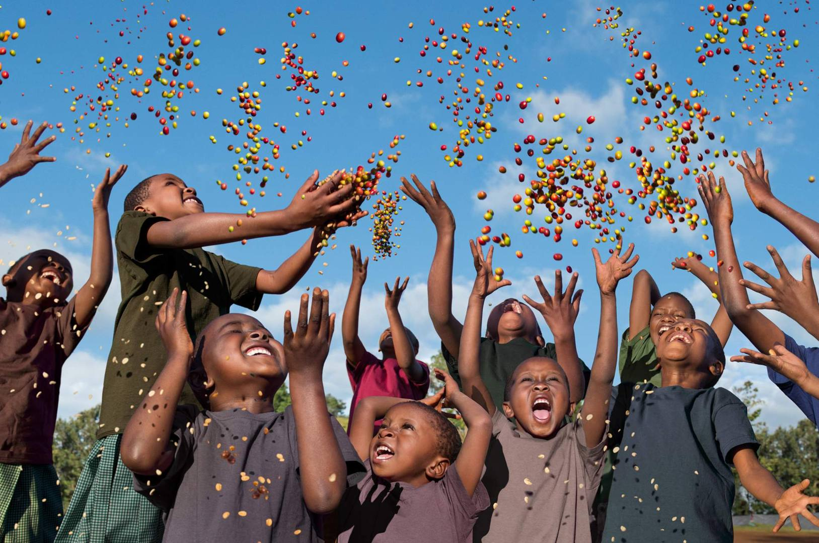 'Future in Our Hands' - children in Father Peter's School in Tanzania who symbolise the Earth Defenders of the future, throwing colourful coffee seeds into the air demonstrates that the future really does lie in our own hands
