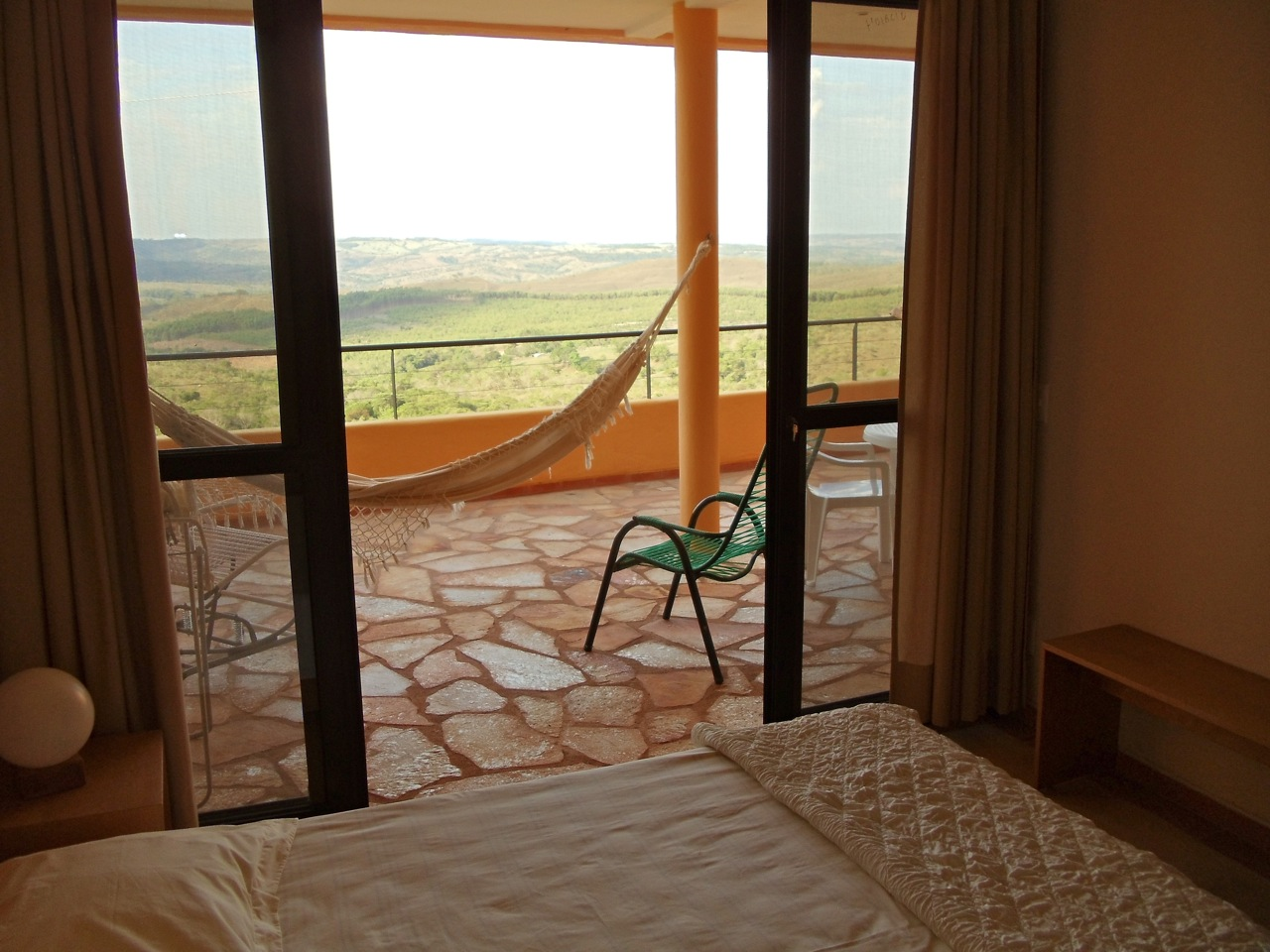 From the bedroom of Alegria, across the spacious, covered private veranda/lanai, opening up to the endless lush green rolling hills surrounding Abadiania.