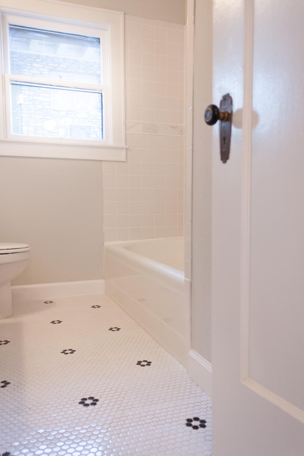 White hex tile with black florets in bathroom