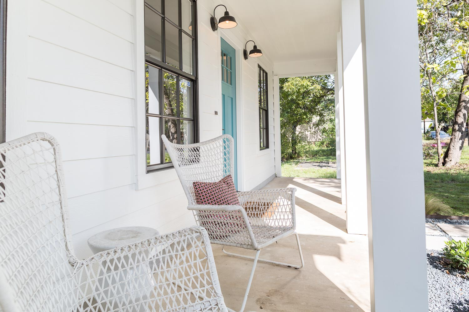 Modern Farmhouse front porch with bell school house light fixtures, white large columns, black windows, and aqua door.