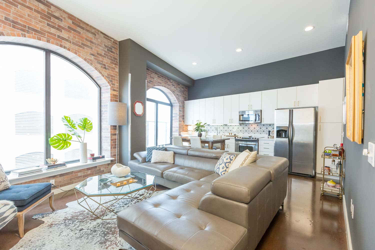 After - We added the brick at the arched windows and selected Sherwin Williams Deep Spacethe walls. The cabinets were painted white and gold hardware was added. The stained concrete floors were complimented with the cowhide rug. We worked with the existing taupe leather sofa.