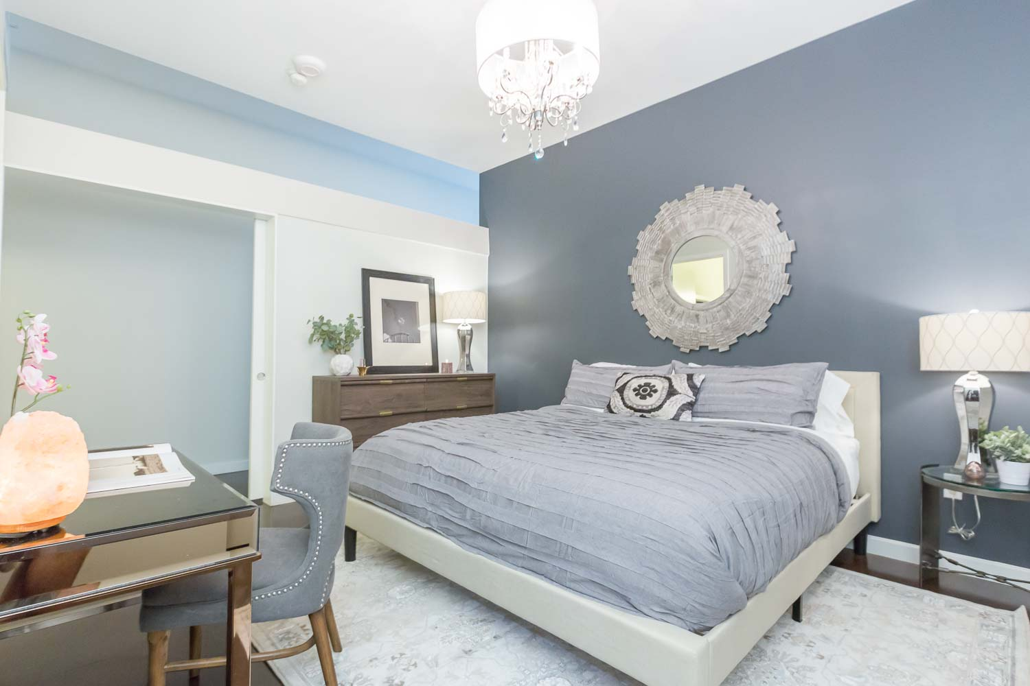 """The master bedroom does not have a window, so it was important that we added """"depth"""" and interest. We did this by painting the headboard wall with Sherwin Williams Deep Space. The chandelier adds luxury as does the gray bedding, mirrored console and walnut dresser with gold accents."""