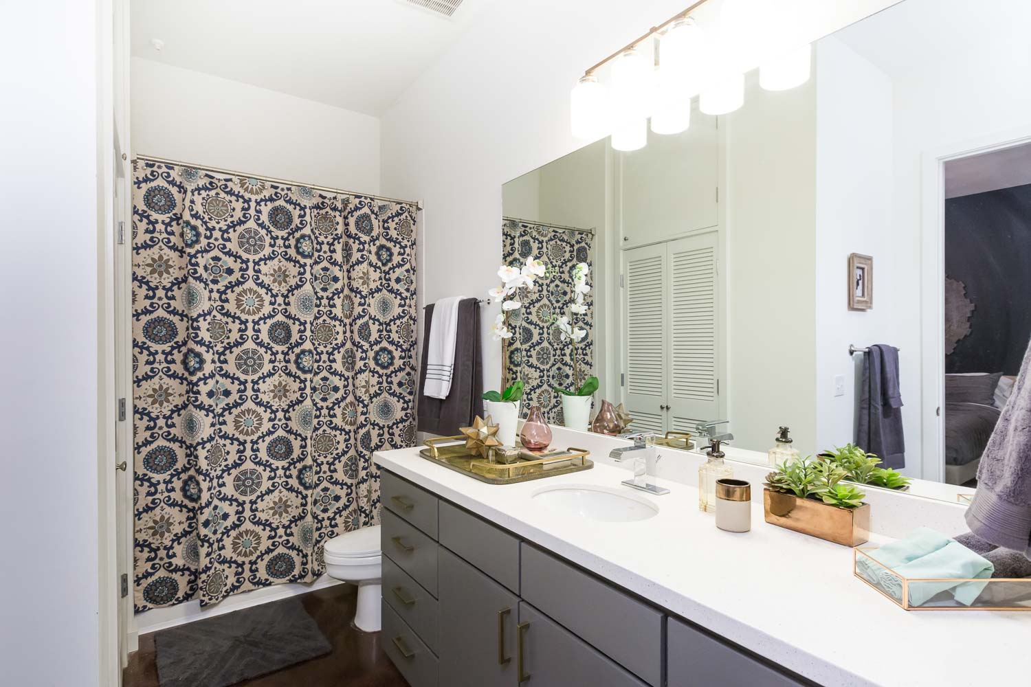 The bathroom simply received a new light fixture, bold shower curtain, and gray paint with gold pulls for the cabinets.