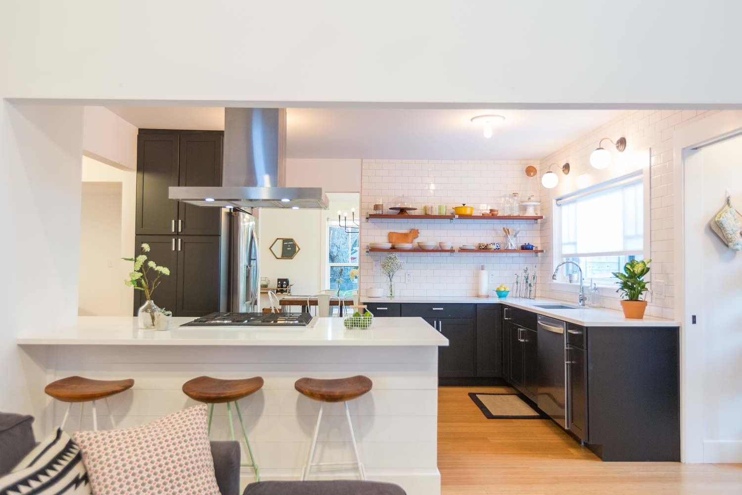 Who wouldn't love this awesome kitchen Making Modern Home designed. At the center of the home, we had to be strategic with the layout. The black cabinets and white quartz countertops, combine nicely with the wood floating shelves and wood barstools.
