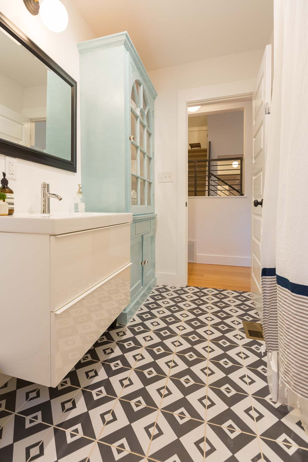 We love the guest bathroom with the bold black and white tile patterned floor. We reused the original dining room hutch as a linen cabinet. It sings in a soft aqua color. The modern ikea vanity was an affordable addition.