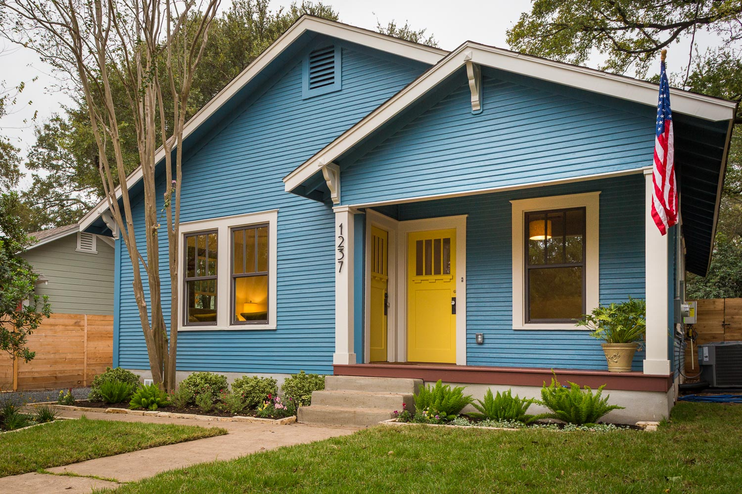 Fully Restored 1930 East Austin bungalow with painted front porch, added vintage corbles, blue siding with yellow front door.  New black windows from Plygem are 3 over 1 traditional style. The modern mission style house numbers are one of my favorite features and came from a local hardware store (Breed and Co)