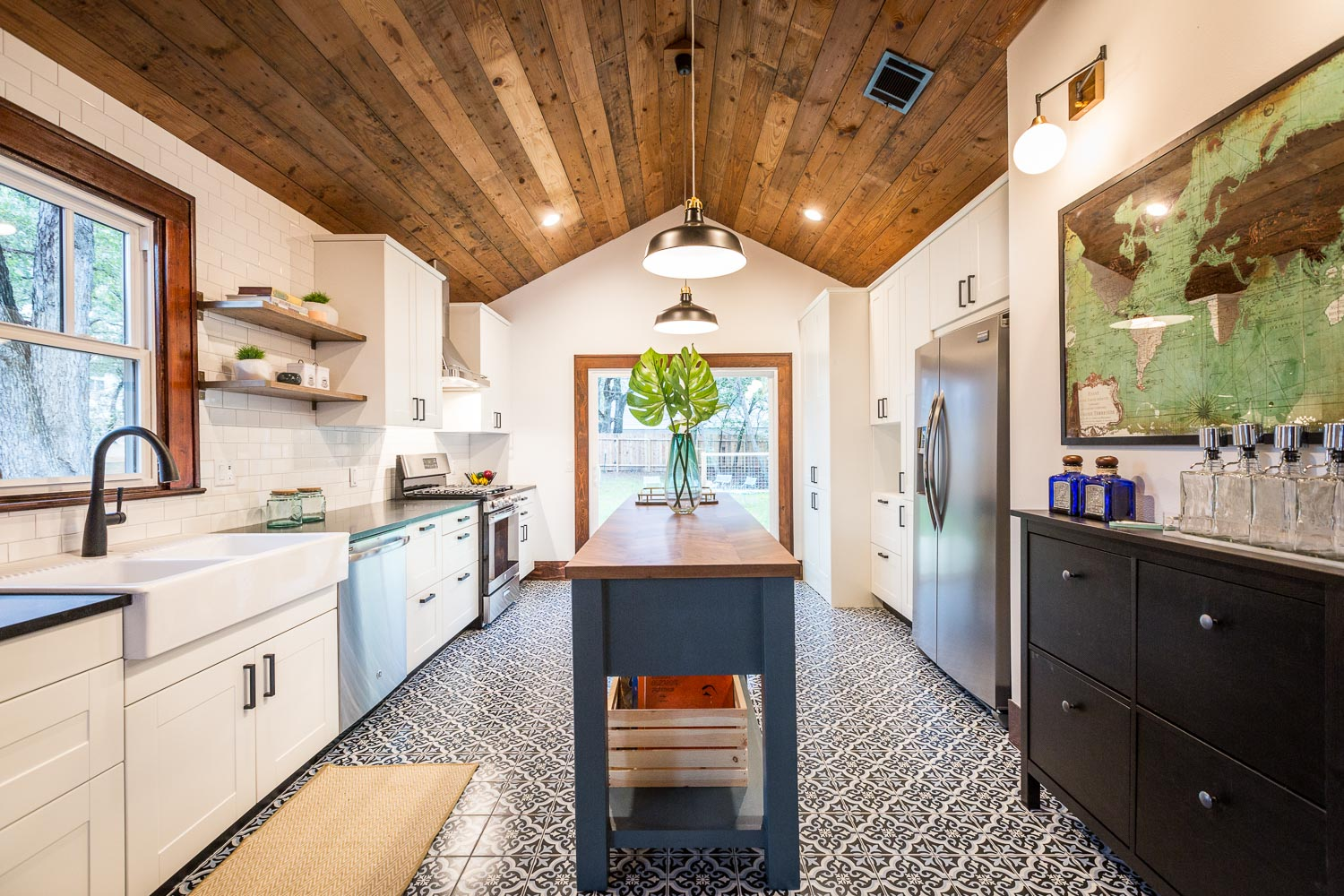 The incredible kitchen was made by combining 2 rooms. The sliding door leads to the back yard. The Spanish tile / Cementi style tile is actually under $4 a square foot! We vaulted the ceilings and added reused shiplap from the house remodel. Honed black granite countertops, a custom farmhouse teal island with walnut butcher block top, matte black faucet and hardware,floating shelves compliment the Ikea Grimslov shaker style cabinets. The bar to the right is an Ikea shoe shelf which is low profile. Above it is a World Market mirror. We love the kitchen's warmth and personality especially with the original dark wood trim!