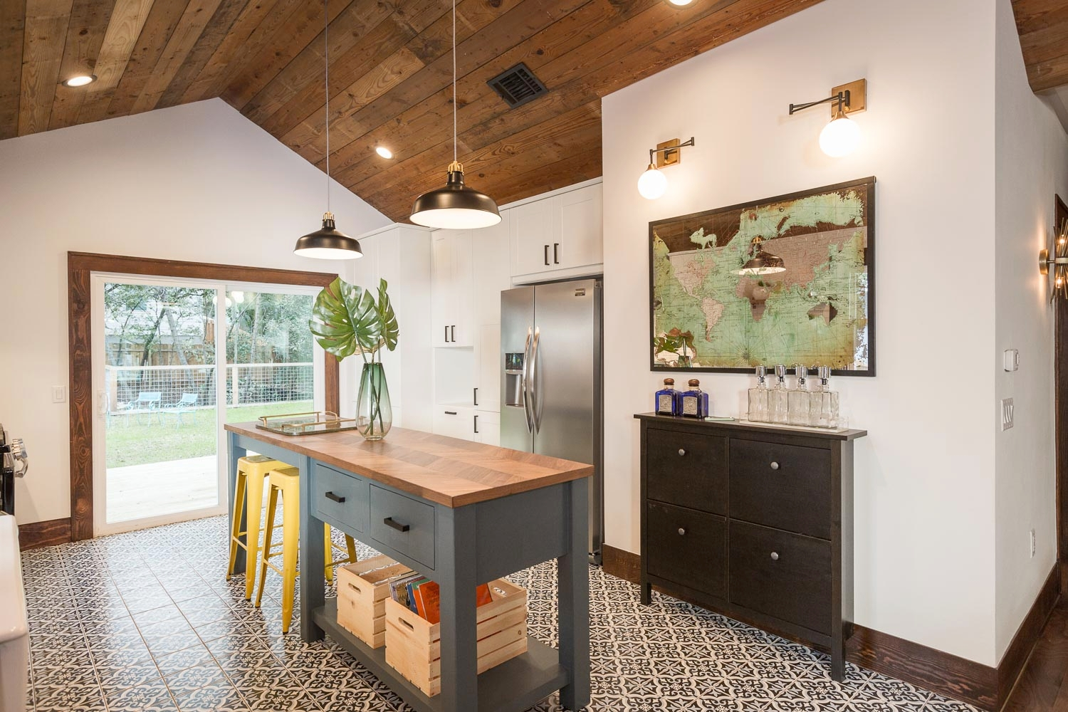 Another view of the bar and teal farmhouse island with walnut butcher block. The yellow barstools stand out and tie into the front door color and gold accents.