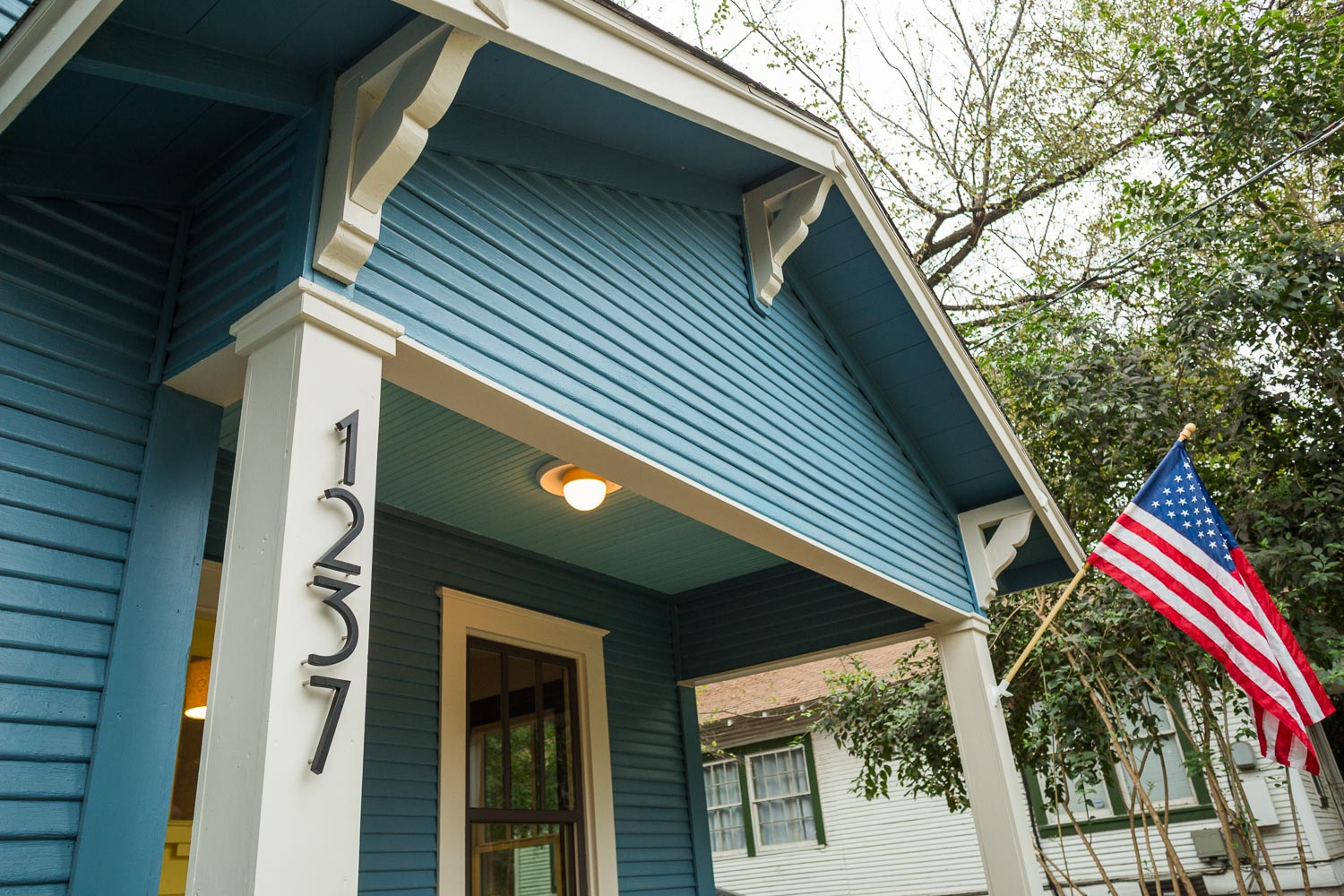 Traditional bungalow porch with thoughtful detailing and the American flag. This bungalow is an American Craftsman classic now!