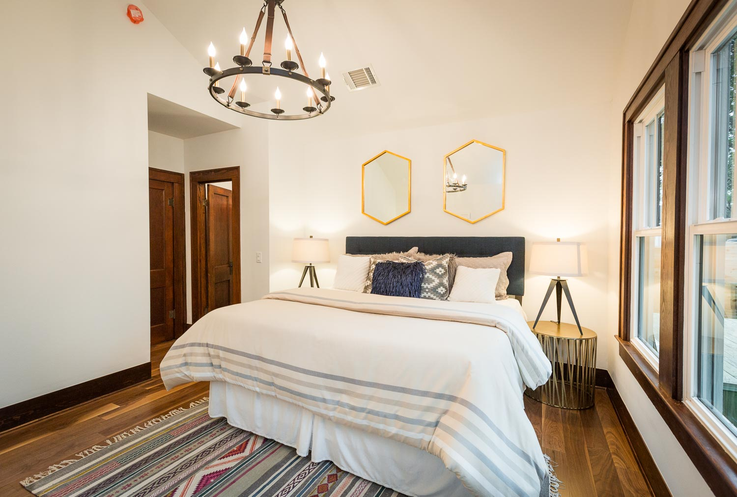 The master bedroom can accommodate a king size bed. The vaulted ceiling, chandelier, walnut floors, and dark wood trim add so much character and warmth to this amazing room.