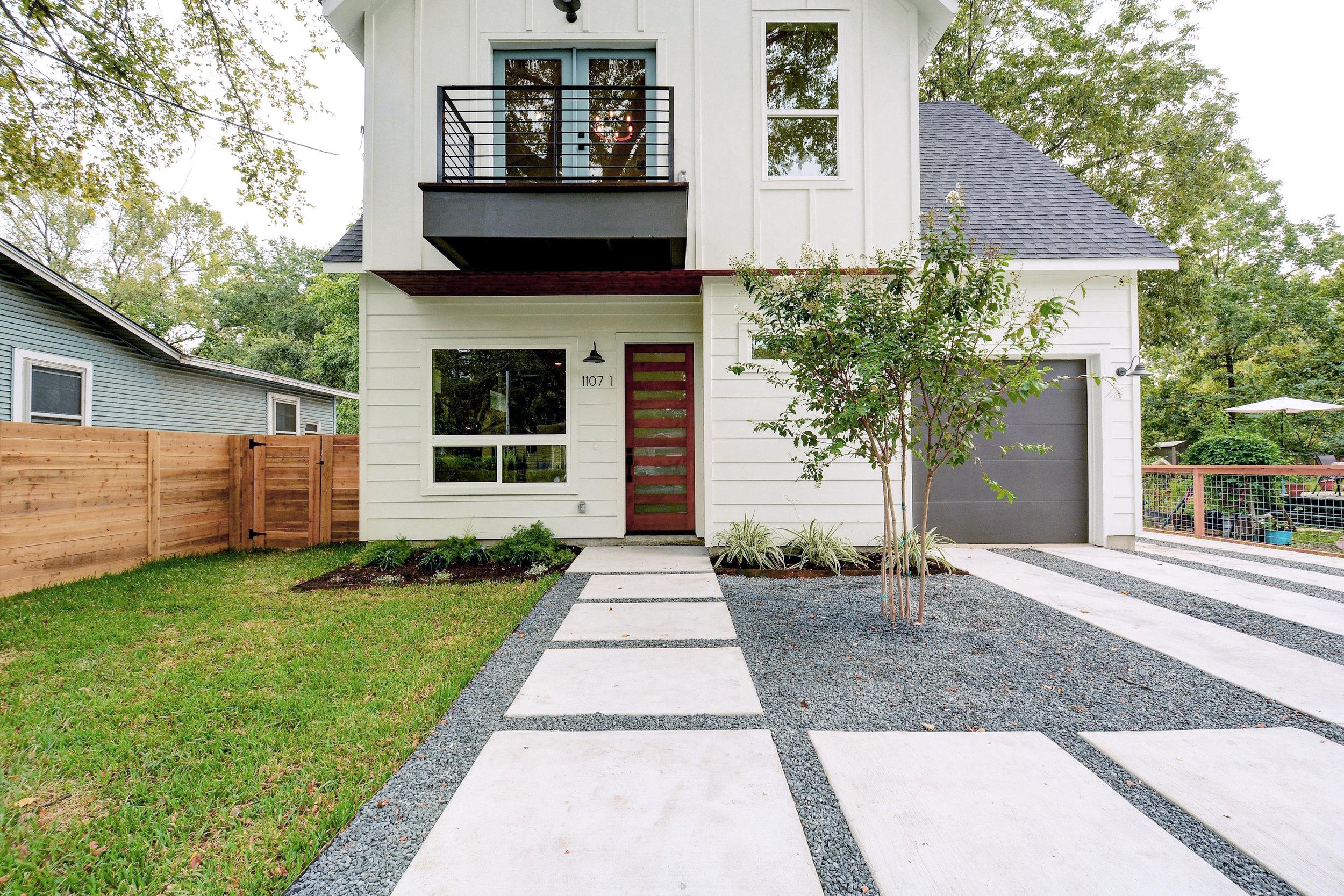 """The charming Modern Cottage architecture is perfect for a white color scheme with wood accents. The modern front door and balcony contrast the barn lights. The french doors are painted Benjamin Moore Seastar and the garage door is my go-to Sherwin Williams """"Urbane Bronze""""."""
