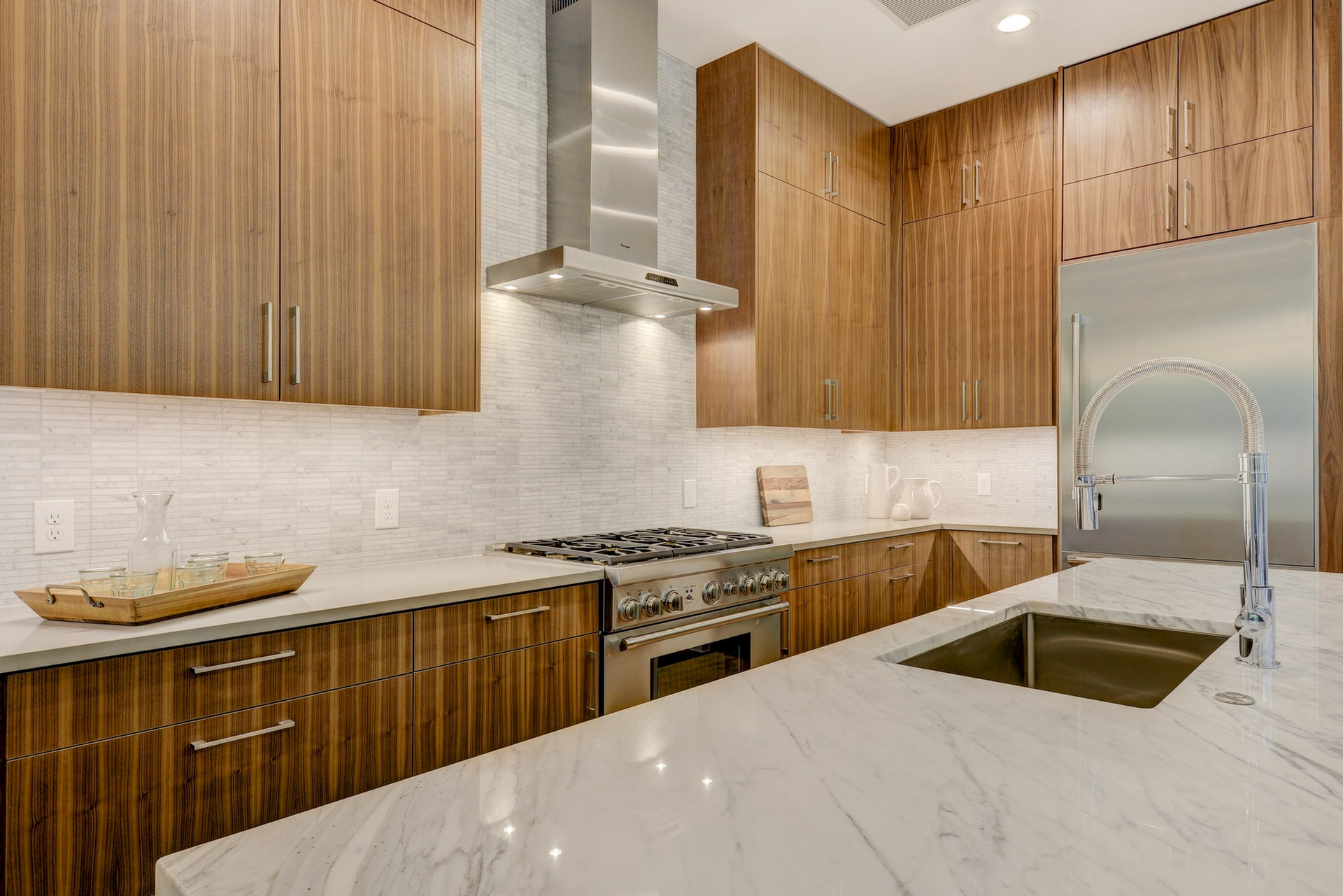 The vertical grain walnut cabinets, Thremador appliances, and calcutta marble countertops add luxury to this kitchen.