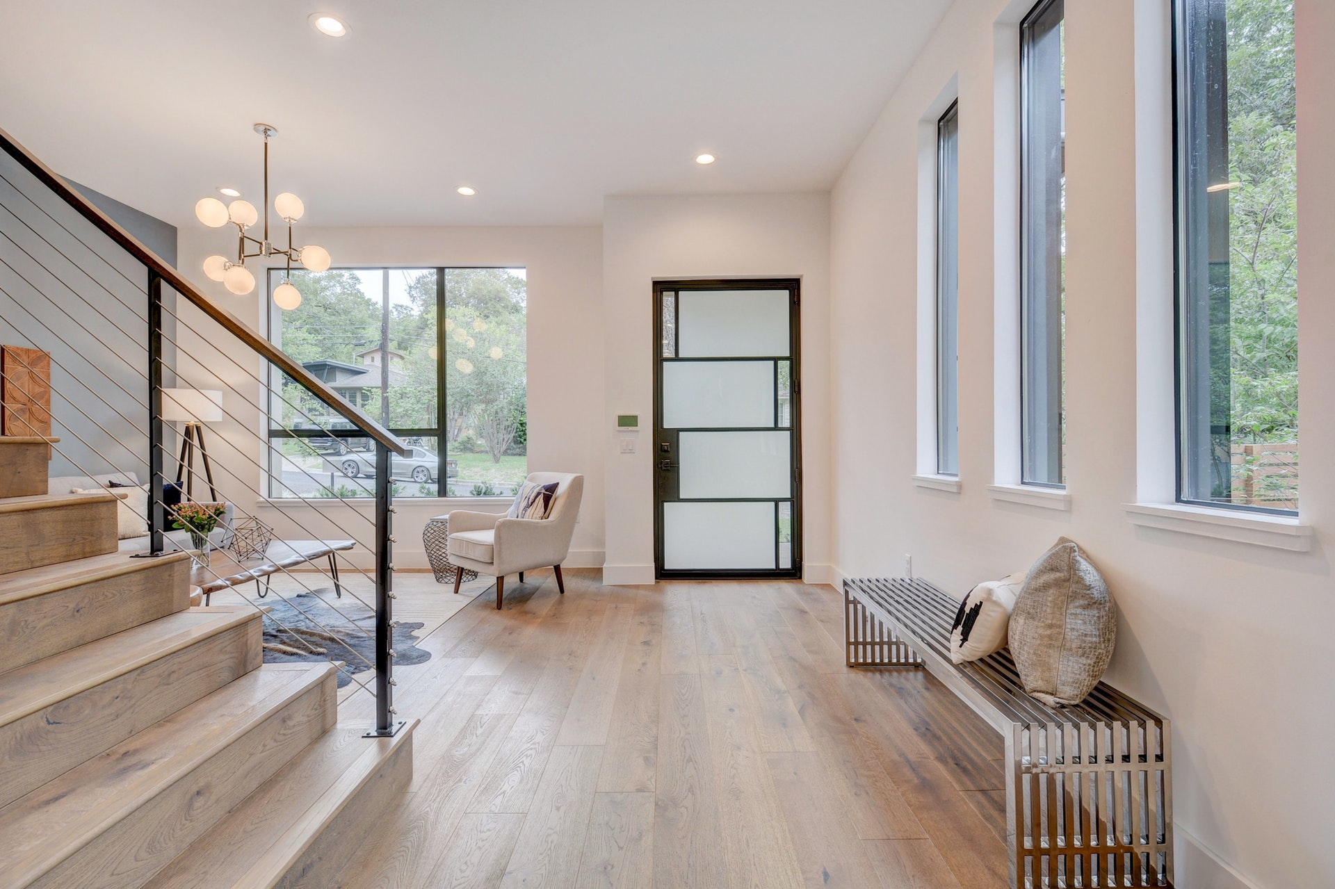 The custom steel and glass Durango door was one of the design starting points. The metal elements are picked up at the cable railing stairwell and the Restoration Hardware Bistro light fixture in the formal living room. This entry foyer is sure to impress.