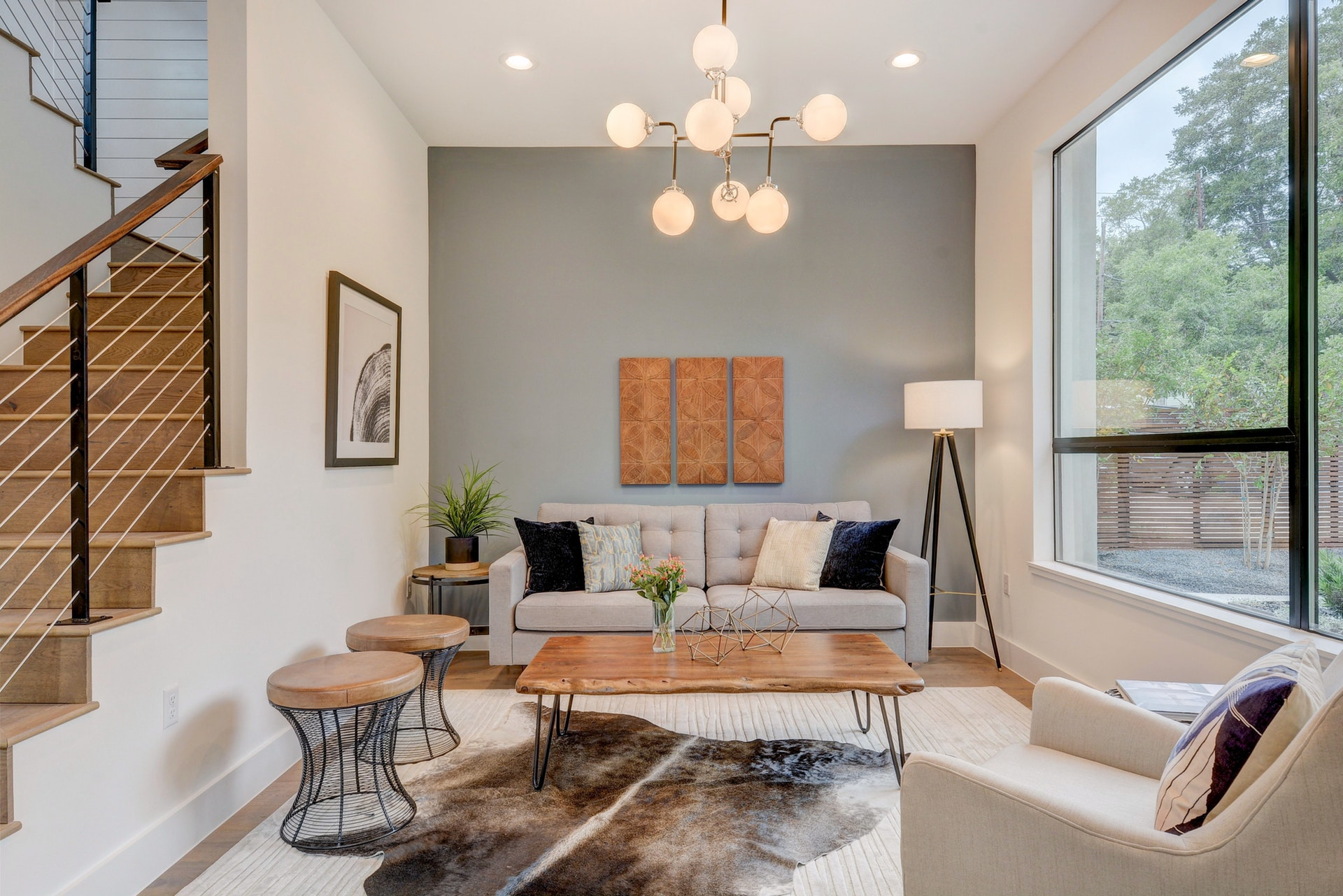 The formal living room includes an accent wall in Benjamin Moore Sea Star, black accents, cognac leather stools, a layered cowhide and mid century modern wood wall panels.