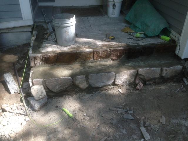 Hand cut fieldstone rise is installed.