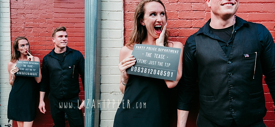 "bachelorette party girl in black dresses poses with bouncer and funny sign saying ""the tease"" near Broadway in Nashville"
