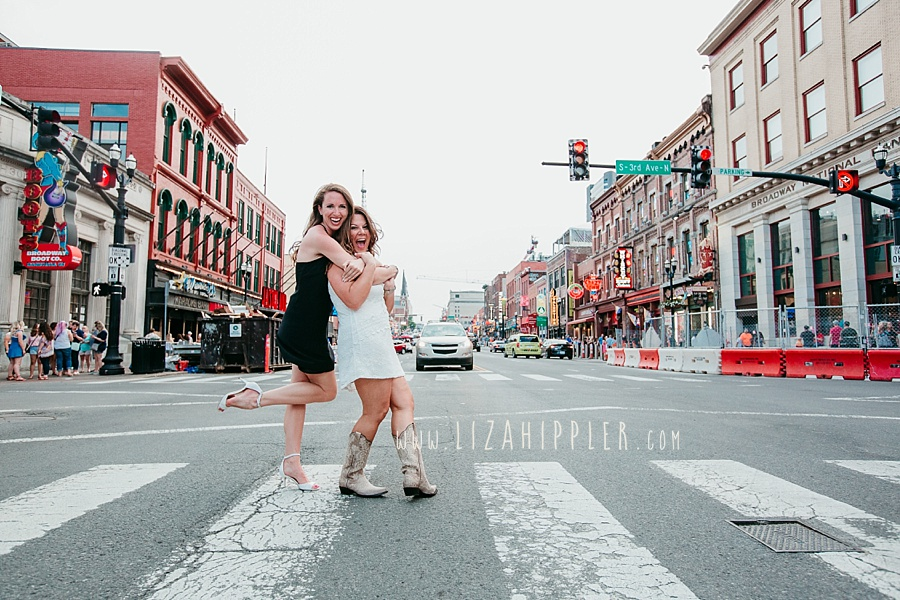 bachelorette and maid-of-honor hugging on 3rd and broadway in nashville tn