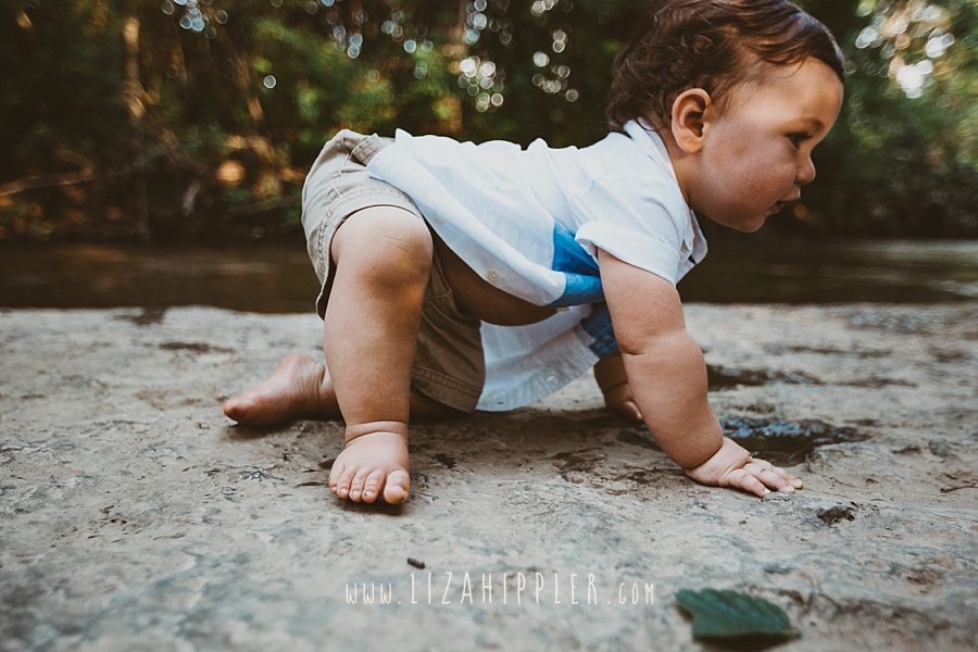 one year old boy crawling on a creek rock