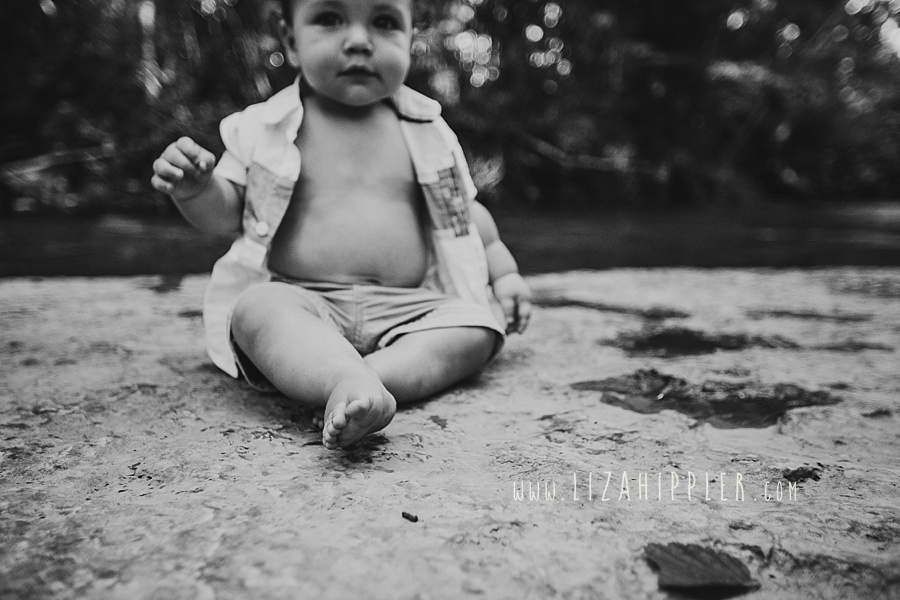 black and white image of baby boy sitting on a large rock