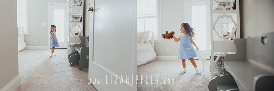 toddler girl in blue dress in white room