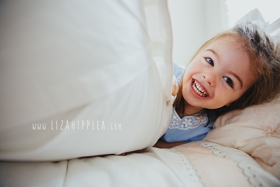 happy little girl peeks out from behind pillows