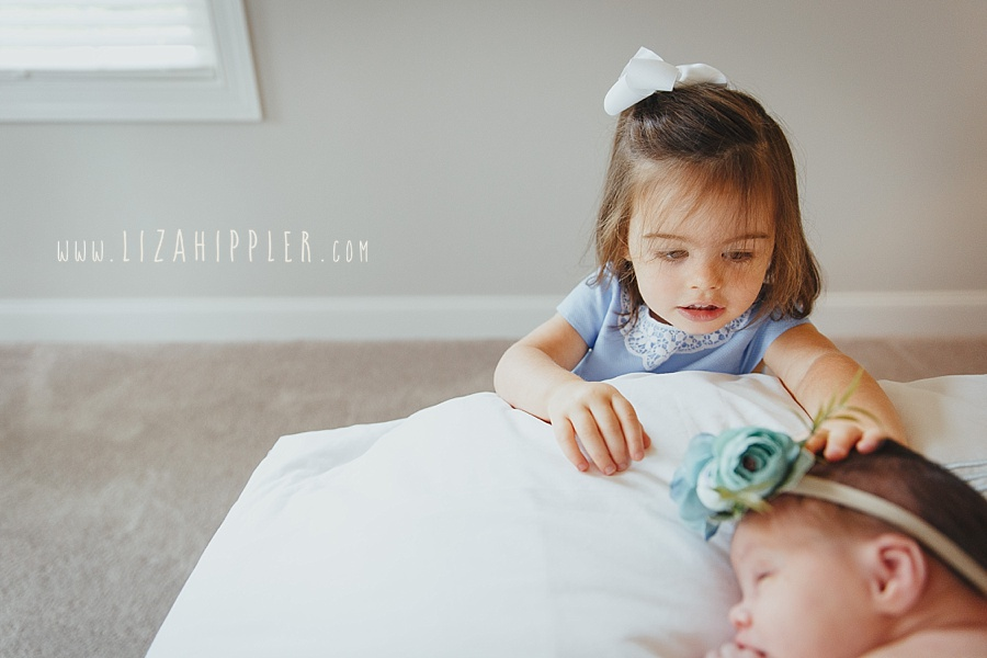 big sister touches new sister's head
