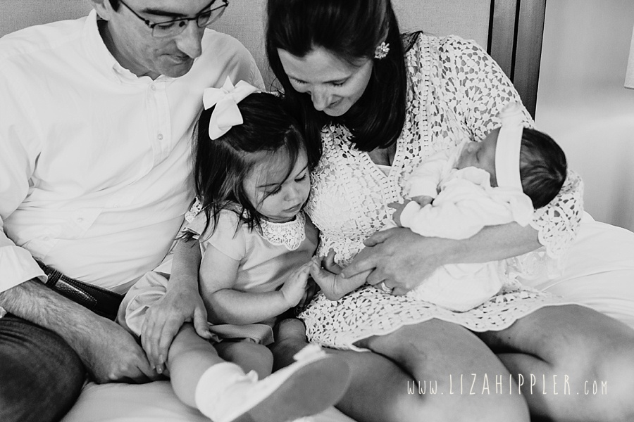 new family of four looks at baby girl's toes